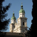 Domes of Salzburg Cathedral stand prominant against a clear blue sky
